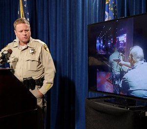 Las Vegas police Undersheriff Kevin McMahill watches body camera footage during a press conference on accusations by Seattle Seahawks player Michael Bennett, Wednesday, Sept. 6, 2017, in Las Vegas.