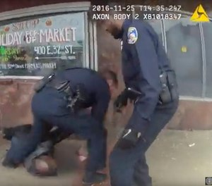 In this image taken from video from a body camera worn by a Baltimore police officer on Monday, Nov. 25, 2016, three officers attend to a man that was shot in Baltimore. The police officers shot the man who was threatening people with knives at a bus stop.