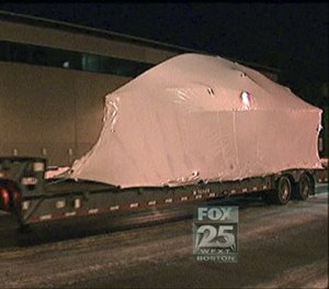 This still image from video provided by Fox25 Television in Boston shows the covered boat in which Dzhokhar Tsarnaev was captured, being transported along a street in Boston, early Monday, March 16, 2015. (AP Photo/Fox25 Television)