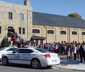 In this Monday, Oct. 6, 2014 photo, Massachusetts College of Liberal Arts students, faculty and staff are evacuated into the armory in North Adams, Mass., following a bomb threat on campus. The school was evacuated for three hours until the campus was deemed safe. Nearly a dozen public schools and colleges in Massachusetts, New Hampshire and Connecticut have received threats forcing evacuations and cancellations in the past week. (AP Photo/The Berkshire Eagle, Gillian Jones)