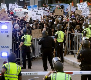 In this May 31, 2020, file photo, protesters, background, demonstrate outside a police station in Boston, over the death of George Floyd who died after being restrained by Minneapolis police officers.