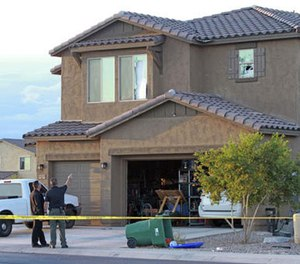 Police point to the window of a Maricopa home on Tuesday, Sept. 27, 2016, where a Border Patrol agent was found dead inside after exchanging gunfire with officers responding to a domestic violence call. (Howard Waggner/Maricopa Monitor via AP)