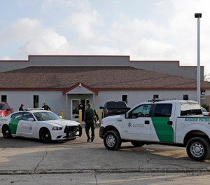 A U.S. Border Patrol Agent walks between vehicles outside the Central Processing Center in McAllen, Texas (AP Photo/David J. Phillip, File)