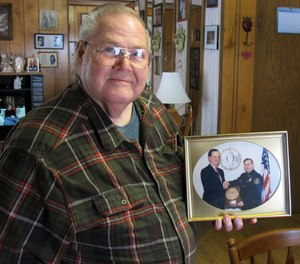 Former Richford police chief Richard Jewett holds a photo of himself in Highgate, Vt., shaking hands with former FBI Director William Sessions. Jewett was being honored for the night in 1987 when he apprehended a man who carried a bomb into the United States from Canada. At a time when terrorism is part of the discussion about whether to build a wall on the U.S. southern border to protect the country, the Richford incident was the only one of its kind when anyone was caught trying to enter the United States illegally as part of a terrorist plot. (AP Photo/Wilson Ring)
