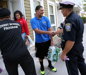 In this Sept. 20, 2018 photo, Francisco Melger, left, of the Boston Center for Youths and Family, and Police Officer Dan Long greet East Boston residents during a Walk for Peace and Unity. Nearly three years after the nation's largest single takedown of MS-13 gang members, residents in the strongly Central American communities around Boston say the streets are noticeably quieter.