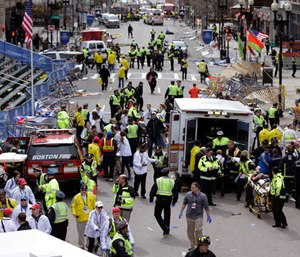 In this April 15, 2013, file photo, medical workers aid injured people following an explosion at the finish line of the 2013 Boston Marathon in Boston.