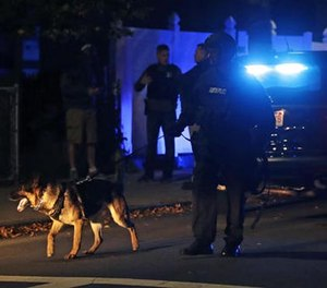Police search for a suspect after a shooting in the East Boston neighborhood of Boston, Wednesday, Oct. 12, 2016. (AP Photo/Charles Krupa)