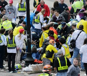 In this Monday, April 15, 2013 file photo, medical workers aid injured people at the finish line of the 2013 Boston Marathon following an explosion in Boston. Over 13,000 videos and 120,000 photos were sent to police during the investigation.