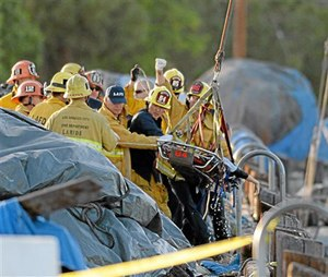 Firefighters remove a lifeless body, believed to be child from the water after a car went off the berth and into the water at the San Pedro Slip, in San Pedro, Calif., Thursday, April 9, 2015. The two children pulled from the submerged vehicle were hospitalized in grave condition, authorities said. (AP Photo/The Daily Breeze, Steve McCrank)
