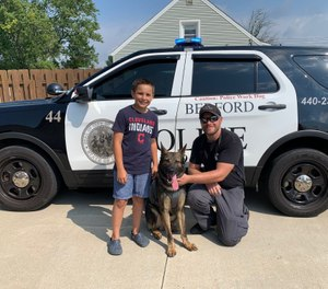 Brady Snakovsky, 10, stands with a Bedford Police officer after donating a vest to K-9 Luca on August 25, 2020 in Bedford, Ohio. (Photo/Bedford Police Department)