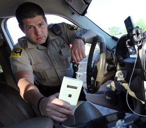 In this Sept. 21, 2015 photo, Minnehaha County Deputy Sheriff Elliott Crayne installs a car breathlyzer for a participant in the state's 24/7 Sobriety Program outside the county jail in Sioux Falls, S.D.