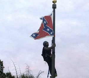 Bree Newsome of Charlotte, N.C., climbs a flagpole to remove the Confederate battle flag at a Confederate monument in front of the Statehouse in Columbia, S.C.