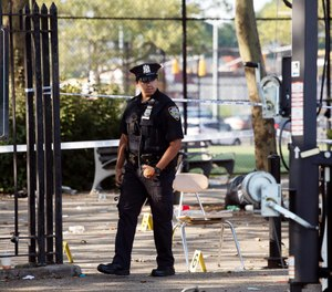 A police officer walks by yellow evidence markers at a playground in the Brownsville neighborhood in the Brooklyn borough of New York, Sunday, July 28, 2019. (AP Photo/Mark Lennihan)