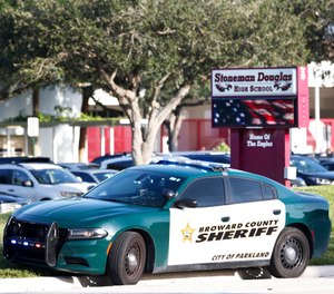 A Broward County Sheriff's Office vehicle is parked outside Marjory Stoneman Douglas High School, Wednesday, Aug. 15, 2018, in Parkland, Fla. (AP Photo/Wilfredo Lee)