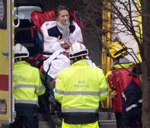A woman is evacuated in an ambulance by emergency services after a explosion in a main metro station in Brussels. (AP Photo/Virginia Mayo)