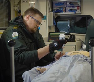 A robotic glove worn by a paramedic allowed a doctor to remotely perform an ultrasound scan on a mannequin representing a patient during a demonstration by the University Hospitals Birmingham and telecommunications company BT. (Photo/BT)