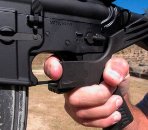 In this Oct. 4, 2017 file photo, a shooting instructor demonstrates the grip on an AR-15 rifle fitted with a