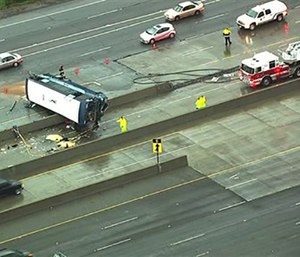 The bus flipped on its side while traveling north on Highway 101, California. (KGO-TV via AP)