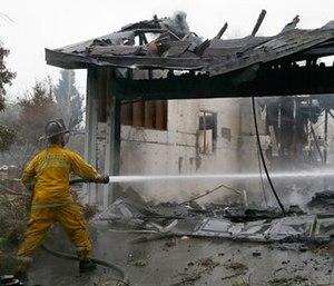 A Santa Rosa firefighter hoses down a hotspot in the Coffey Park area of Santa Rosa, Calif.