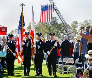 A U.S. flag hangs from the ladder of a fire truck as a color guard comprised of Santa Rosa firefighters presents the colors to start a Day of Remembrance memorial for victims of California wildfires. (AP Photo/Ben Margot)