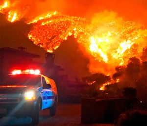 Fire burns canyons and ridges above Bella Vista Drive near Romero Canyon as the fight to contain a wildfire continues in Montecito, Calif. (Mike Eliason/Santa Barbara County Fire Department via AP)