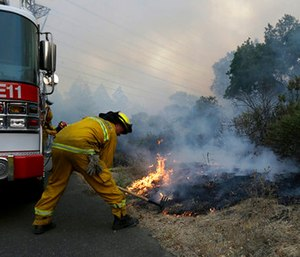 Santa Rosa firefighters work on a fire on the side of a road near the Oakmont area in Santa Rosa, Calif.