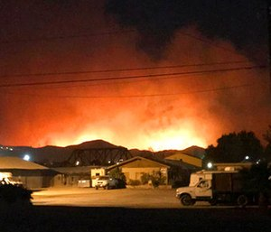 Flames from a wildfire loom up over a neighborhood in Santa Paula, Calif. (Megan Diskin/The Ventura County Star via AP)