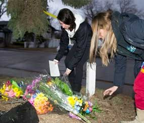 Unidentified women leave flowers at the scene of the multiple fatal stabbing in northwest Calgary, Alberta on Tuesday, April 15. (AP Image)