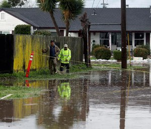 Residents walk down a flooded road on Monday, Feb. 20, 2017, in Salinas, Calif.