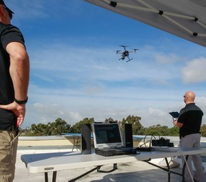 Police officer Laurence Meyerowitz (right) and retired captain Fritz Reber (left) watch a drone land that is being piloted from a remote room in the building during a practice and training program on Friday in Chula Vista, Calif. (Photo/TNS)