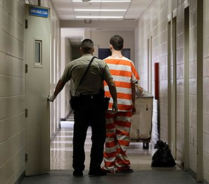 In this Feb. 21, 2013 file photo, an inmate at the Madera County Jail is taken to a housing unit at the facility in Madera, Calif. (AP Photo/Rich Pedroncelli)