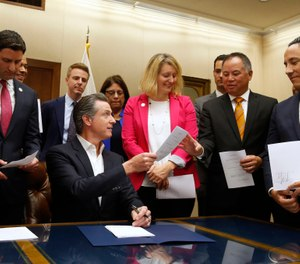 alifornia Gov. Gavin Newsom, seated hands Assemblyman Phil Ting, D-San Francisco, second from right, a copy of his bill that Newsom signed at the Capitol in Sacramento, Calif., Friday, Oct. 11, 2019. (AP Photo/Rich Pedroncelli)