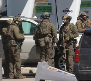 Royal Canadian Mounted Police officers surround a suspect at a gas station in Enfield, Nova Scotia. (Photo/AP)