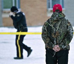 A man holds a rosary as police investigate the scene of a shooting at the community school in La Loche, Saskatchewan.