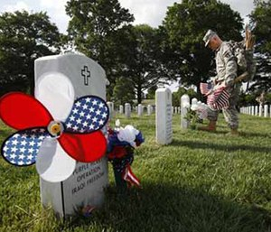 "In Section 60, where many of the soldiers who fought in Iraq and Afghanistan are buried, Captain James Leggett, of Alexandria, Va., with the 3rd U.S. Infantry Regiment, or ""Old Guard,"" places flags before each grave in preparation for Memorial Day, during the annual ""Flags-In"" at Arlington National Cemetery in Arlington, Va., on Thursday, May 24, 2012. (AP Photo/Jacquelyn Martin)"