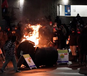 A trash can burns as people take part in a protest against police brutality, late Sunday, Jan. 24, 2021, in downtown Tacoma, Wash., south of Seattle. (AP Photo/Ted S. Warren)