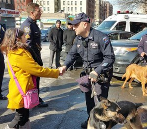 Savannah Solis, left, is greeted by a New York City police officer while visiting a police precinct in the Bronx, Tuesday, Feb. 24, 2015. (AP Image)