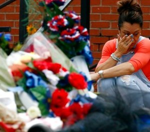 Katrina Ebbers, whose husband is a Lincoln County Sheriff's deputy, cries as she sits near the makeshift memorial for slain Lincoln County Sheriff's Office deputy William Durr at the Lincoln County-Brookhaven Government Complex in Brookhaven, Miss., Tuesday, May 30, 2017. (AP Photo/Rogelio V. Solis)