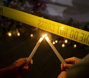 Olina Ortega, left, and Austin Gibbs light candles at a sidewalk memorial in front of Emanuel AME Church. (AP Image)