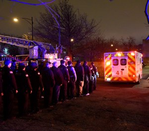 Chicago police officers and firefighters form an honor guard as the body of Chicago Police Officer Samuel Jimenez is brought to the coroner Monday, Nov. 19, 2018, in Chicago.  (AP Photo/David Banks)