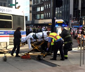 A victim receives help after a bus crash at the corner of Lake Street and Michigan Avenue in Chicago on Tuesday, June 2, 2015. (Steven Rosenberg/ChicagoTribune/TNS)