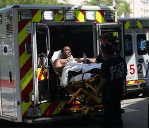 One of three injured firefighters is wheeled into Stroger Hospital on July 31, 2016, after a residential fire.