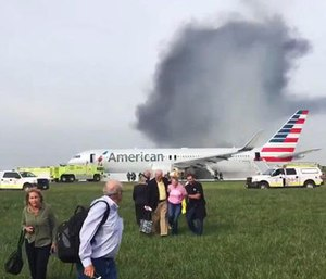 In this photo provided by passenger Jose Castillo, fellow passengers walk away from a burning American Airlines jet that aborted takeoff and caught fire on the runway at Chicago's O'Hare International Airport on Friday, Oct. 28, 2016. (Jose Castillo via AP)
