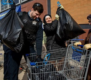 Officer Frank Johnson works with Sister Jaime Mitchell, right, and others to pack bags of food into a wagon on Tuesday, March 24, 2020, at Mission of Our Lady of the Angels in Humboldt Park. (Photo/TNS)