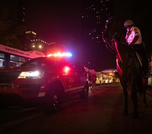 In this Thursday, July 4, 2019 photo, A Chicago Police Department (CPD) officer secures a path for ambulance after reports of stabbings and threatening injuries after the 4th of July celebrations at Chicago's Navy Pier. Police said a false report of gunfire set off a stampede that trampled more than a dozen people. (AP Photo/Amr Alfiky)