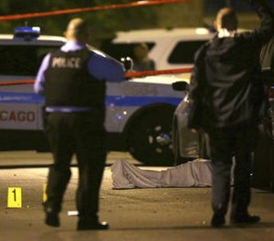 In this May 30, 2016 file photo, police work the scene where a man was fatally shot in the chest in Chicago's Washington Park neighborhood. (E. Jason Wambsgans/Chicago Tribune via AP, File)