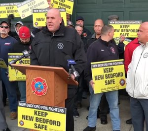 This video screenshot shows a press conference held in February outside Station 11 in New Bedford where union representatives and protesters called for city leaders to not close the station. New Bedford's fire chief announced in February that the station would need to close in order to end controversial blackout policies throughout the city. (Photo/New Bedford Firefighters IAFF Local 841 Facebook)