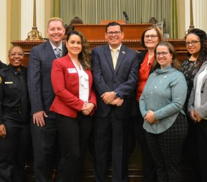 California Assembly Member Rudy Salas (center) introduced Assembly Bill 1945, which was signed by Gov. Gavin Newsom on Friday, reclassifying public safety dispatchers as first responders.