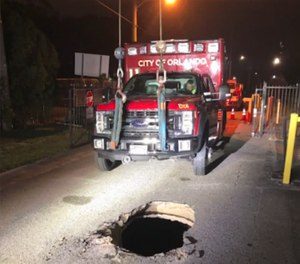 An Orlando Fire Department ambulance had to be lifted up and towed after becoming stuck in a hole initially suspected to be a sinkhole. City officials later clarified that the hole was actually the result of a caved-in stormwater or wastewater line. (Photo/Orlando Fire Department)