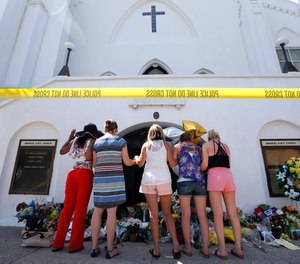 In this June 18, 2015, file photo, a group of women pray together at a makeshift memorial on the sidewalk in front of the Emanuel AME Church, in Charleston, S.C.
